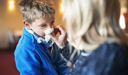 Eine Frau hilft ihrem Kind beim Naseputzen