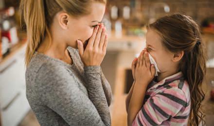 Eine Mutter zeigt ihrer Tochter, wie sie Nasenbluten stoppen kann