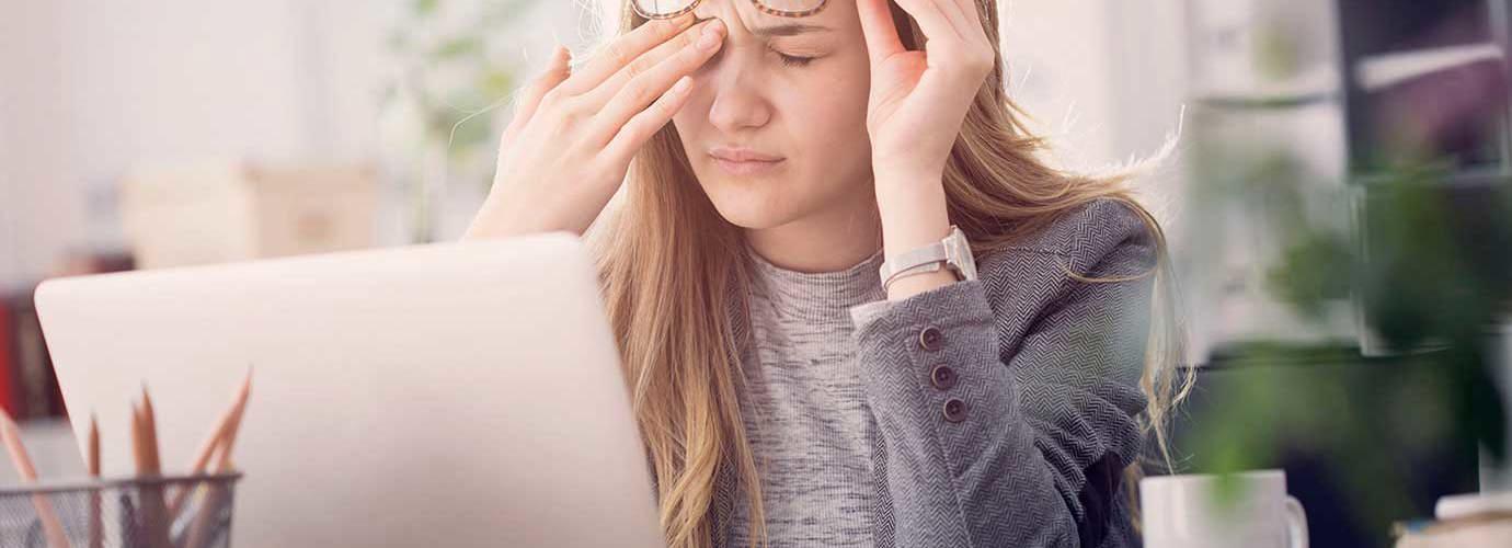 Eine junge Frau leidet unter tränenden Augen während sie an einem Laptop arbeitet