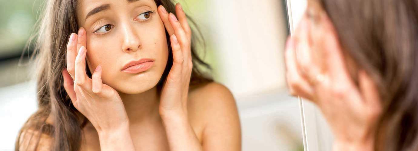 Ein Teenager überprüft von einer Allergie geschwollene Augen in einem Spiegel