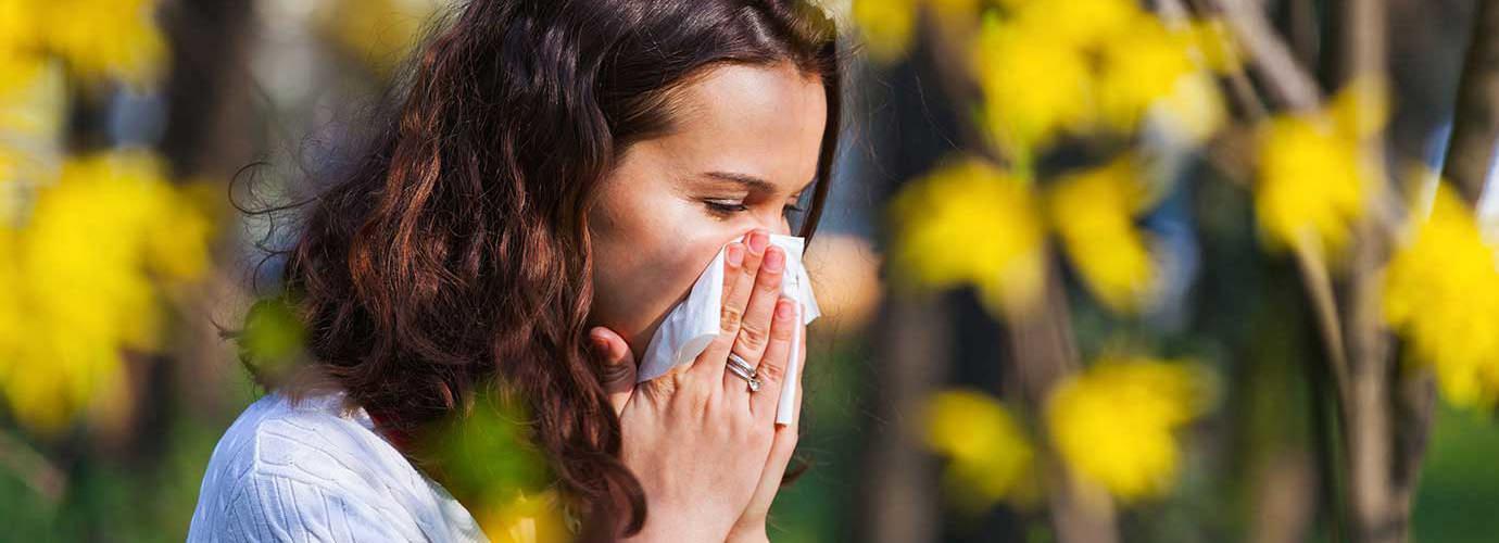 Frau mit Pollenallergie und Erkältung niest im Freien in ein Taschentuch