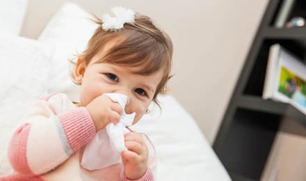 Ein kleines Mädchen putzt sich mit einem Taschentuch die Nase