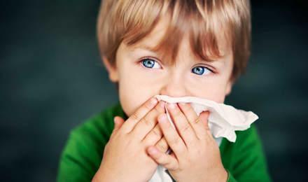 Ein Junge mit Hausstauballergie hält sich ein Taschentuch vor die Nase