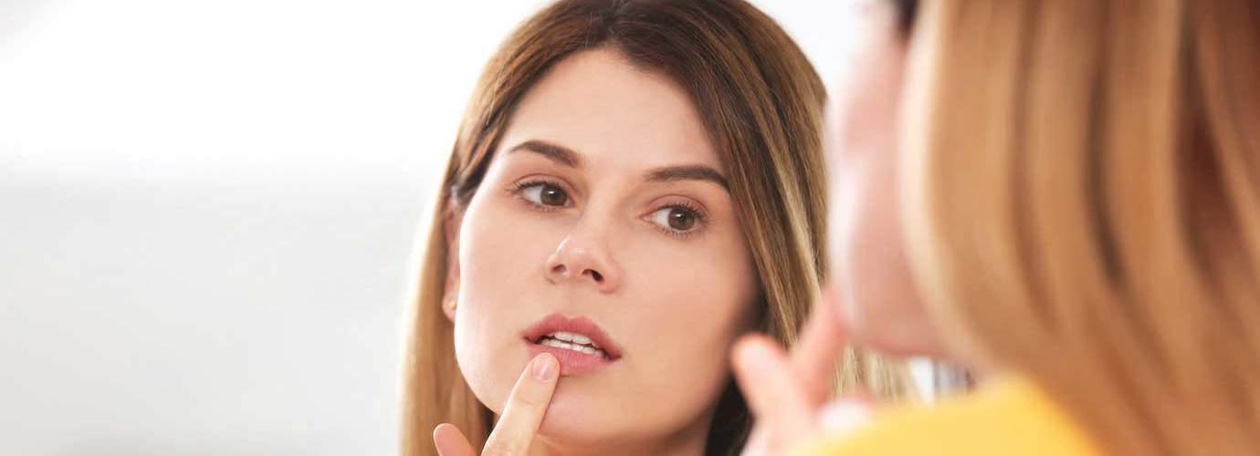 Eine Frau behandelt einen Lippenherpes vor einem Spiegel
