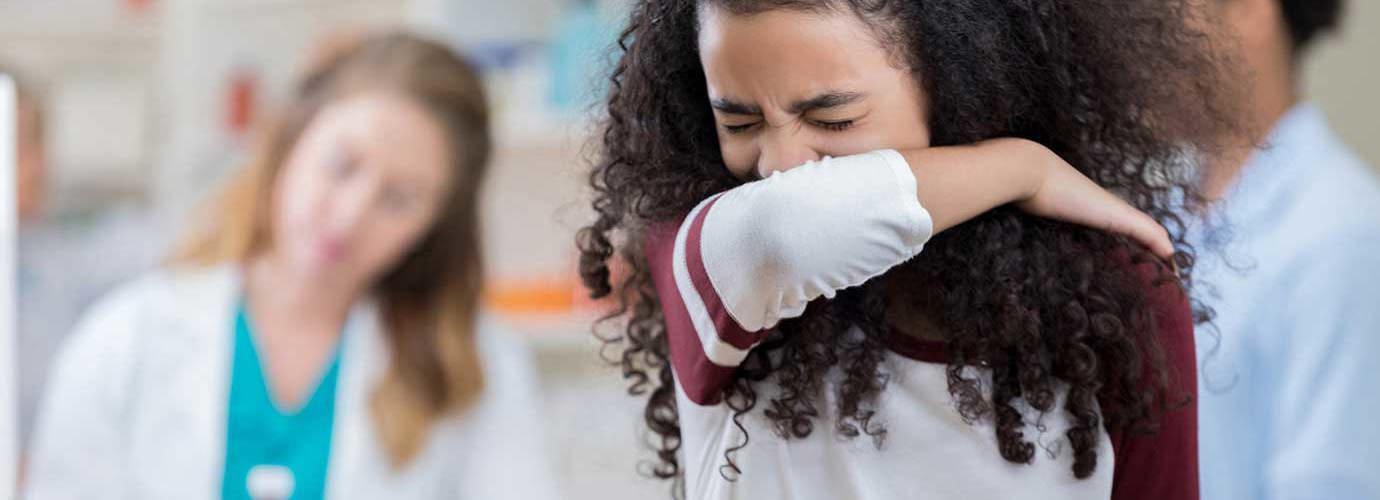 Ein Mädchen niest in ihre Armbeuge