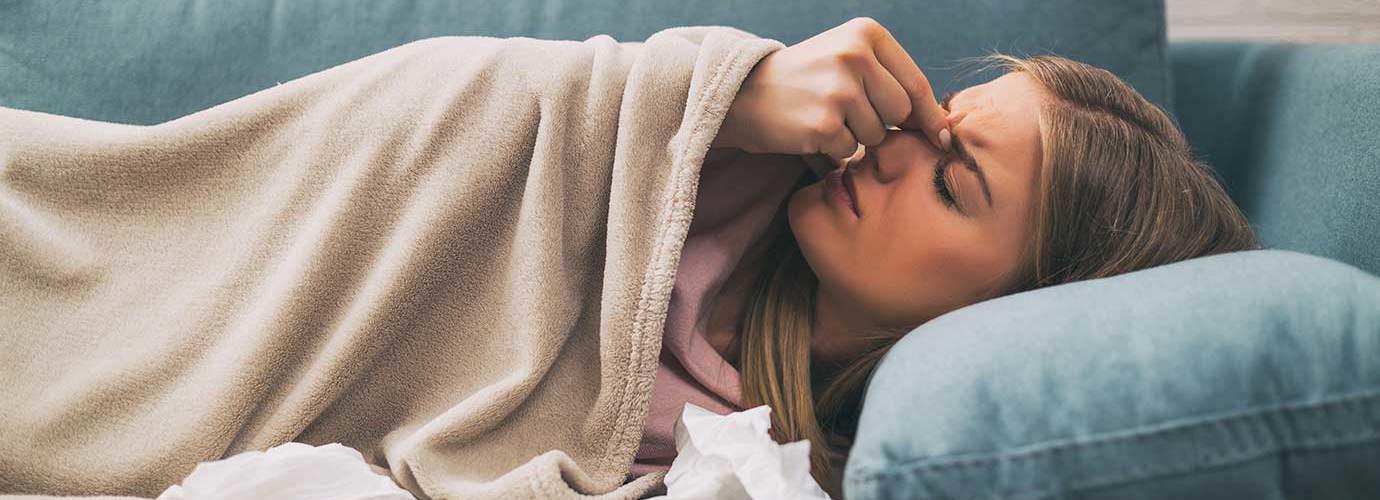Eine Frau mit Nasennebenhöhlenentzündung liegt auf einem blauen Sofa