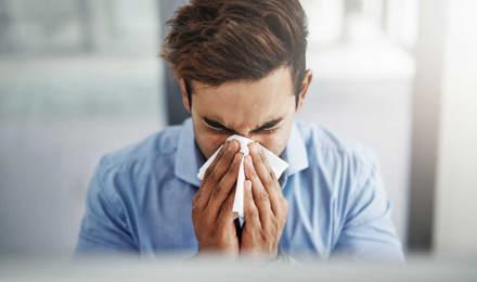 Ein junger Mann schnäuzt sich und putzt sich die Nase mit einem Taschentuch