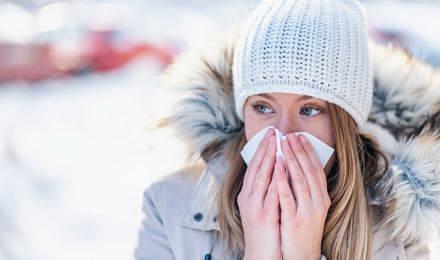 Eine Frau im Schnee schneuzt sich