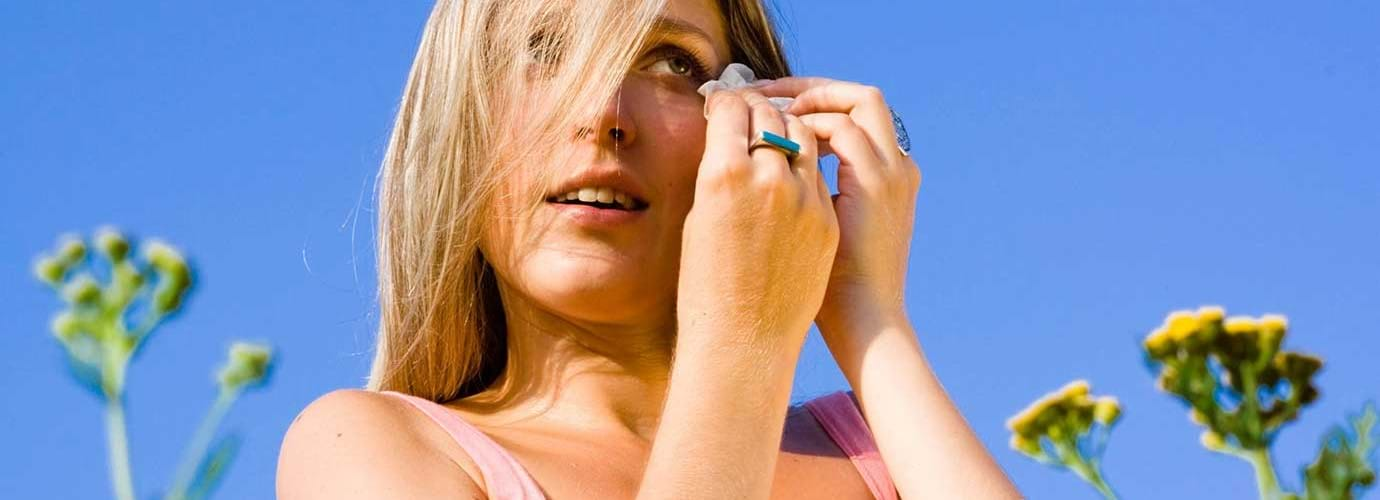 Eine Frau zwischen Blumen leidet an einer Pollenallergie