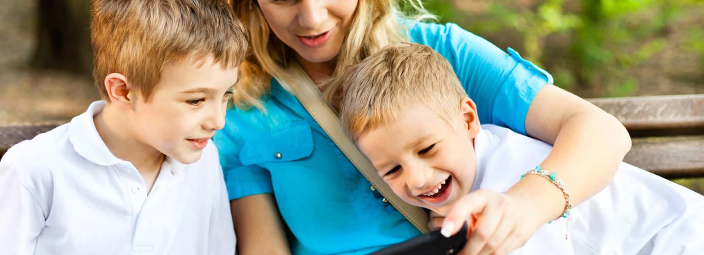 Eine Frau sitzt zwischen zwei kleinen Jungen und zeigt ihnen etwas auf dem Handy