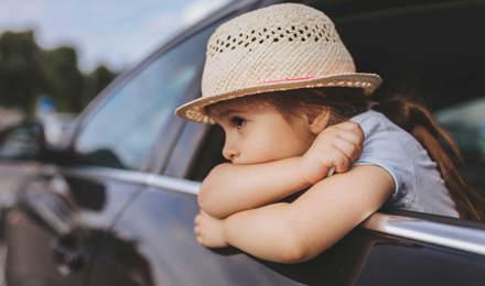 Ein Kind, dem beim Autofarhen übel geworden ist lehnt sich aus dem Autofenster