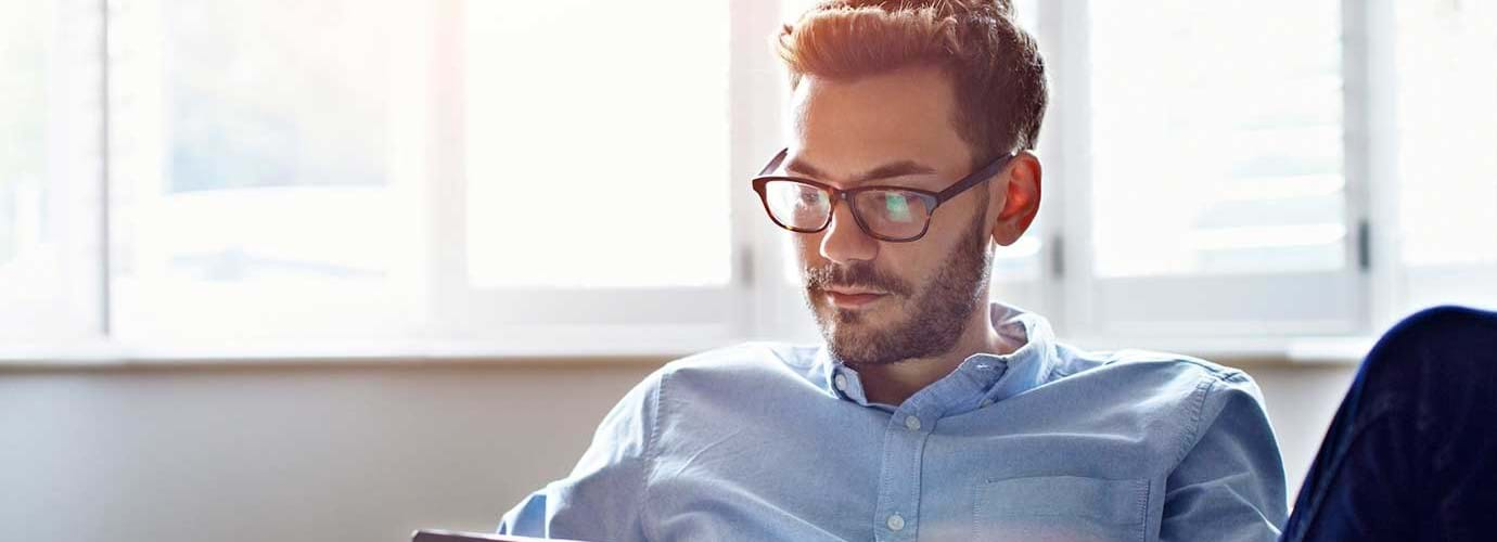 Ein Mann mit Brille sitzt auf einem Sofa und blickt auf ein digitales Tablet