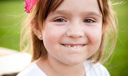 Een jong meisje lacht en laat het gat tussen haar tanden zien, waar haar melktandje net nog kan zijn geweest