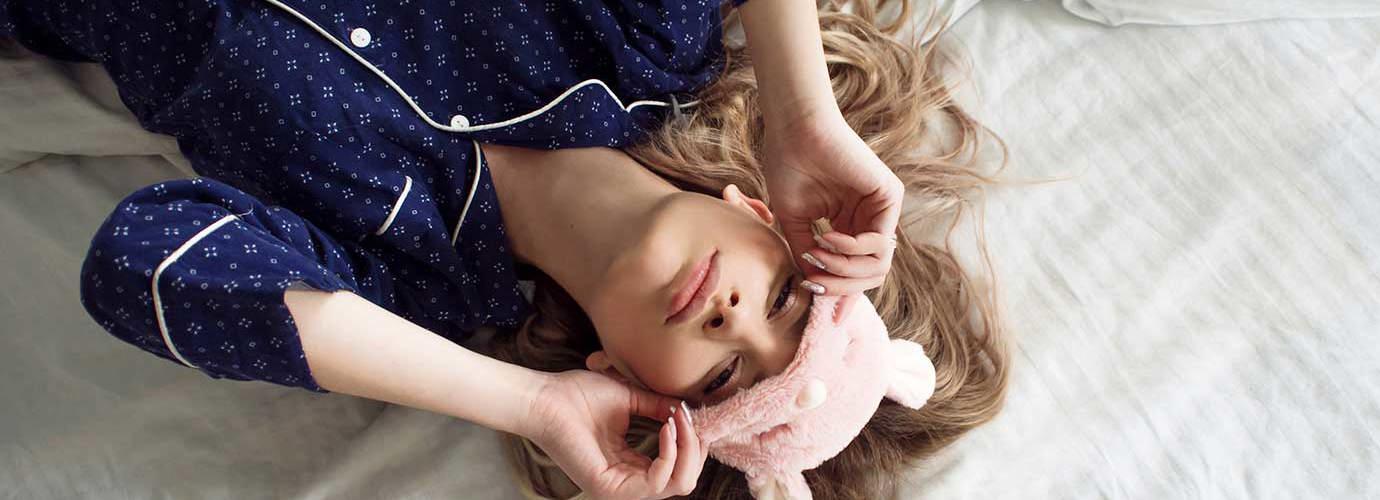 Een kind dat 's nachts een verstopte neus heeft ligt in bed met een oogmasker