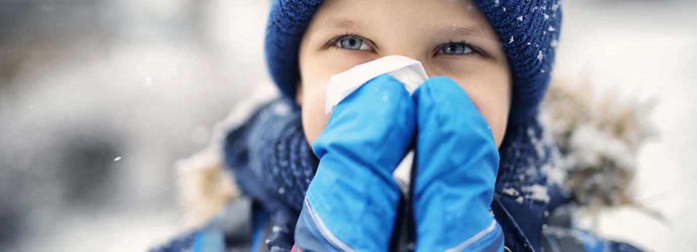 Een klein kind gekleed in winterkleding snuit zijn neus