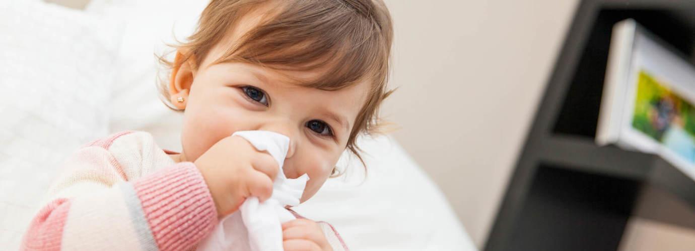 Klein meisje veegt haar neus af met een tissue