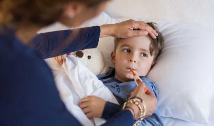 Een kind ligt in bed met een knuffel terwijl een van zijn ouders zijn externe en interne temperatuur opneemt