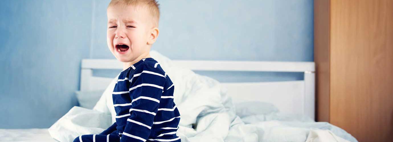 Een jong kind zit op een onopgemaakt bed te huilen