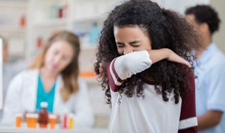Meisje niest in haar arm