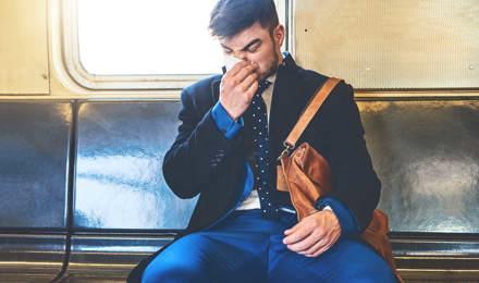 Een man draagt een pak in een treinwagon en snuit zijn neus