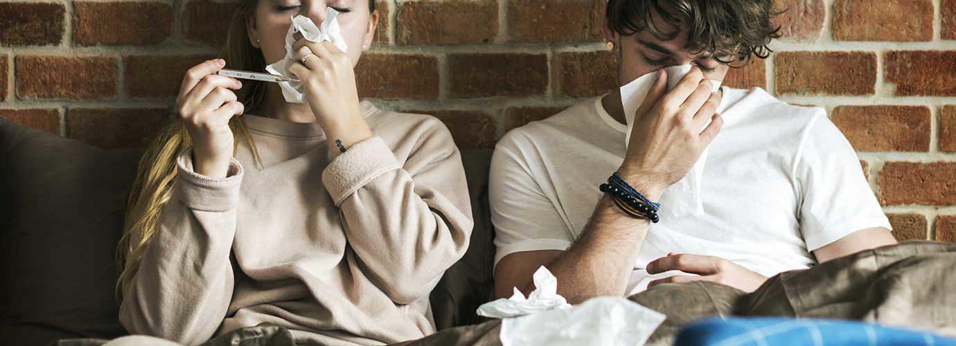 Twee jonge volwassenen zitten onder de dekens te niezen in zakdoekjes met een bakstenen muur in de achtergrond