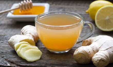 Hele en gehakte gember, honing, citroen en een glas met het mengsel staan op een houten tafel