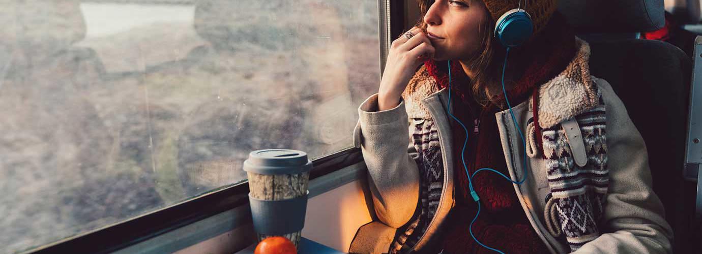 Een vrouw gekleed in winterkleding met print kijkt uit een raam van de trein terwijl ze een koptelefoon draagt