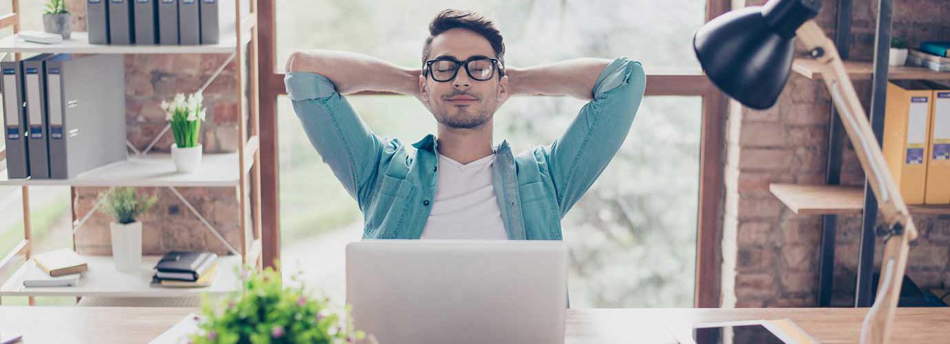 Een zeer ontspannen man leunt achterover in een stoel achter een bureau in een modern kantoor met zijn handen achter zijn hoofd