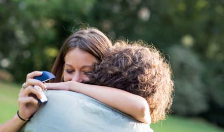 2 personen omarmen elkaar in een tuin terwijl een van hen het doosje van een trouwring vasthoudt