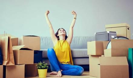 Een vrouw zit te vieren op de vloer van een leeg huis, omgeven door volle kartonnen dozen