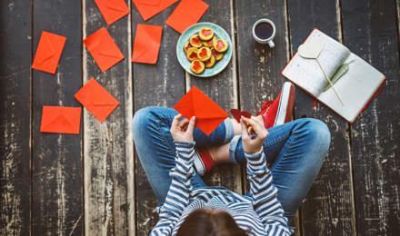 Een vrouw schrijft valentijnskaarten met zelfgemaakte valentijnscadeautjes terwijl ze op de vloer zit