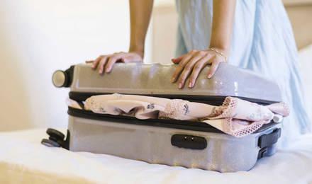 Eine Frau versucht eine Kliniktasche zu schließen