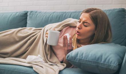 Eine Frau liegt hustend auf dem Sofa und hält eine Teetasse und Taschentücher in den Händen