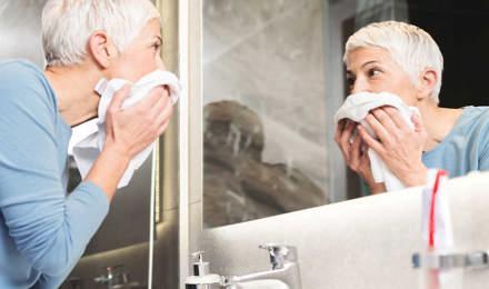 Frau mit kurzen, weißen Haaren sieht sich und ihre trändenden Augen im Badezimmerspiegel an