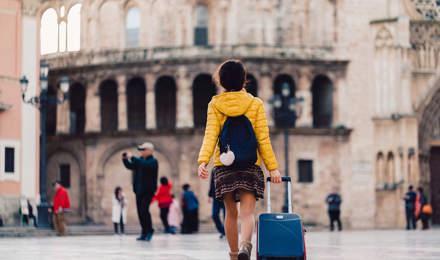 Ein Student läuft in die Richtung eines alten Gebäudes in Valencia