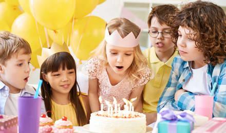 Gruppe junger Kinder an einem Tisch mit Luftballons, Kuchen auf einer Geburtstagsparty für Kinder