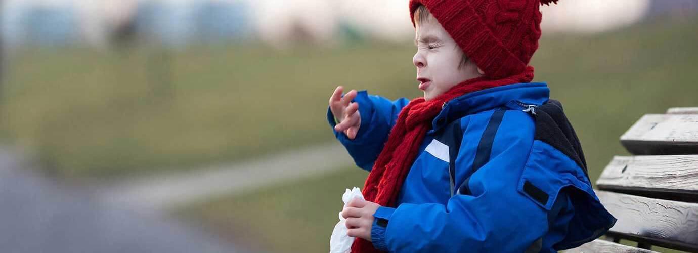 Ein Kind niest auf einer Parkbank im Winter