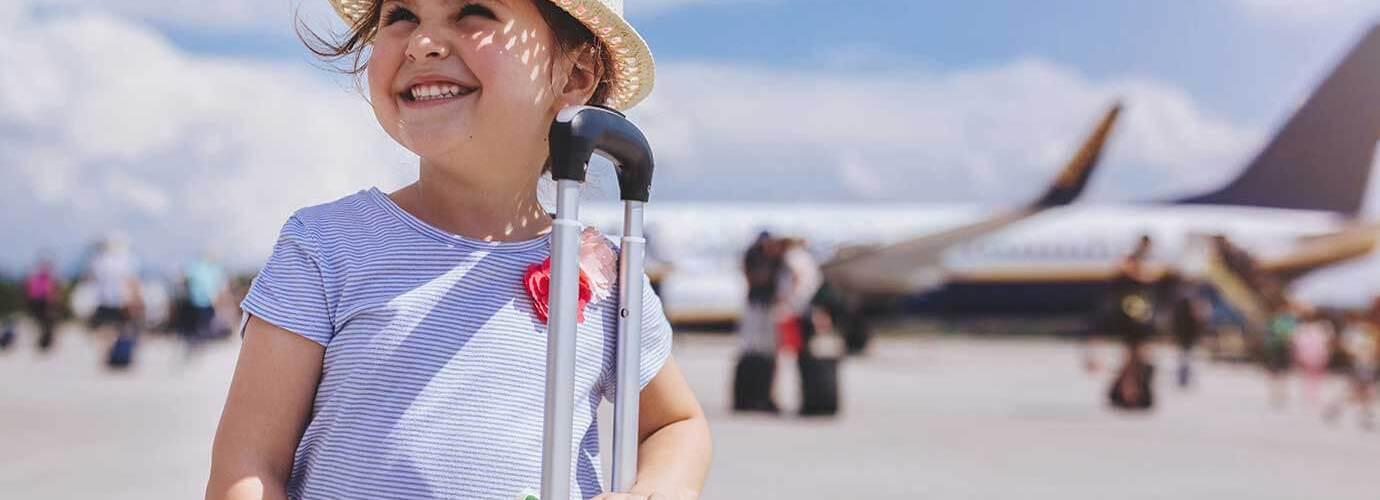 Junges Mädchen lächelnd, mit einem Flugzeug im Hintergrund und einem gelben Koffer im Urlaub