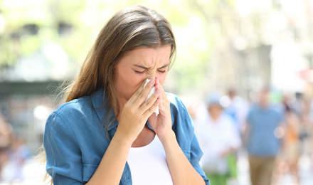 Eine Frau mit Erkältung im Sommer putzt sich die Nase