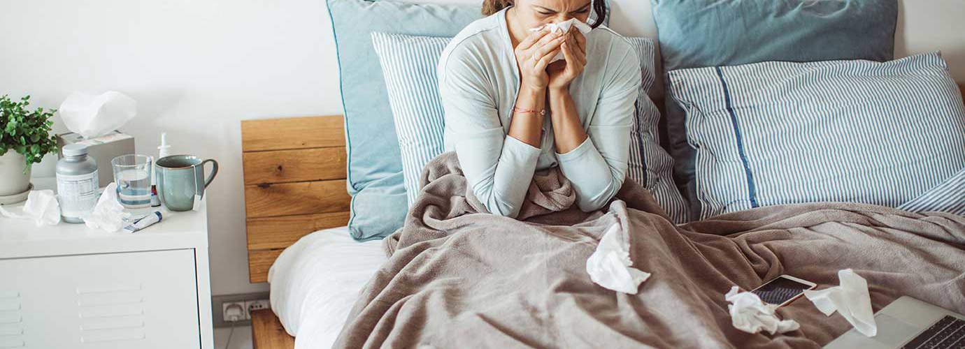 Eine Frau putzt in einem Bett ihre Nase mit einem Taschentuch