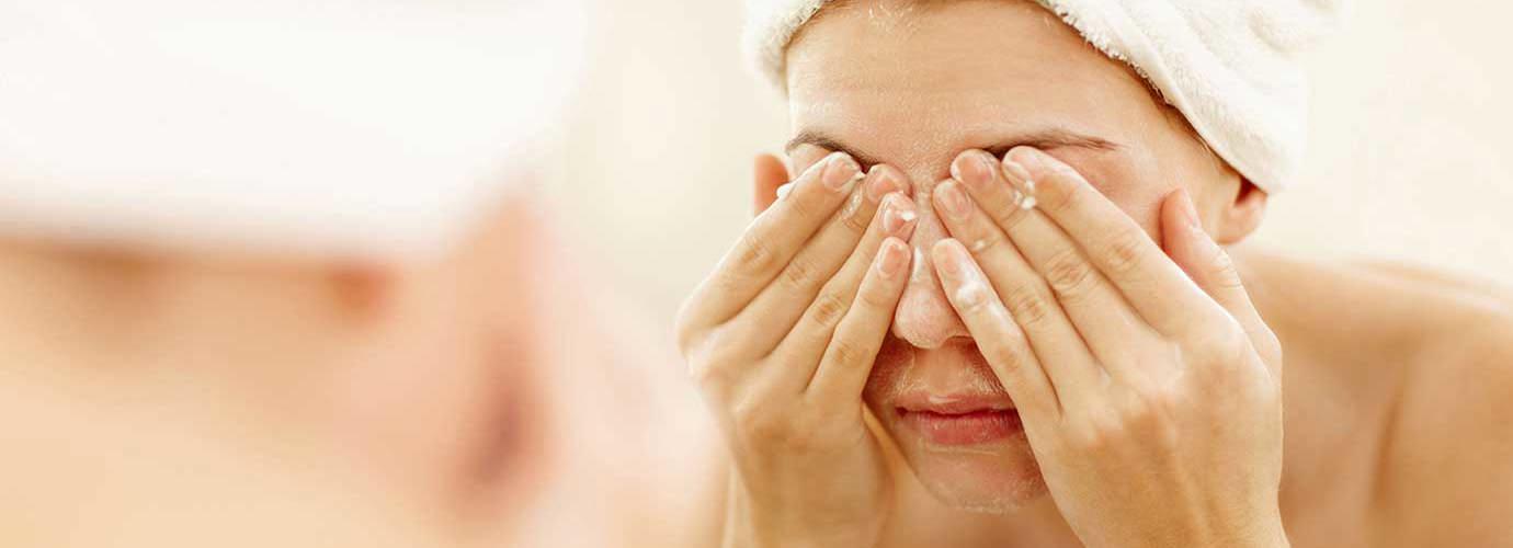 Frau wäscht ihre Augen nach einer Dusche
