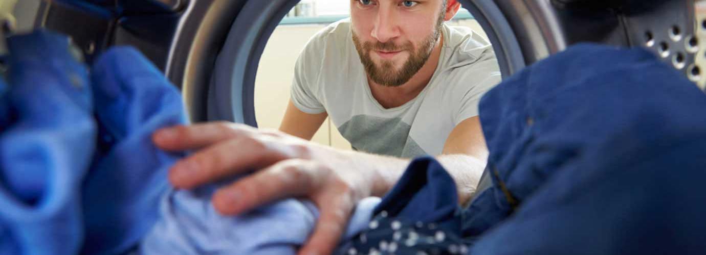 Man reikt naar kleding in de wasmachine