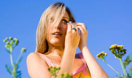 Vrouw tussen bloemen in de zomer met pollenallergie in haar ogen