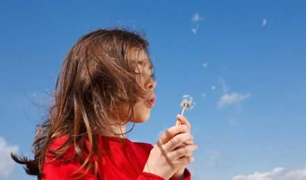 Een jong kind zou huismiddeltjes voor hooikoorts nodig kunnen hebben terwijl ze een paardenbloem blaast met een blauwe lucht op de achtergrond