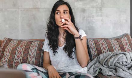 Jonge vrouw met een berkenpollenallergie zit op de bank terwijl ze een neusspray bij haar neus houdt