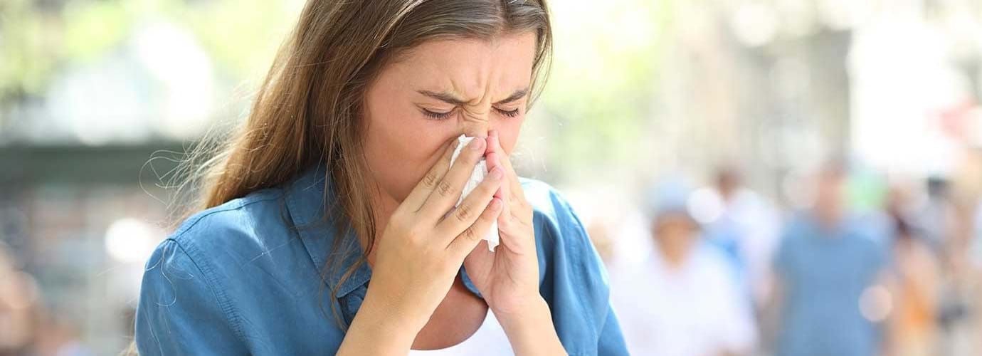 Vrouw met verkoudheid in de zomer snuit haar neus