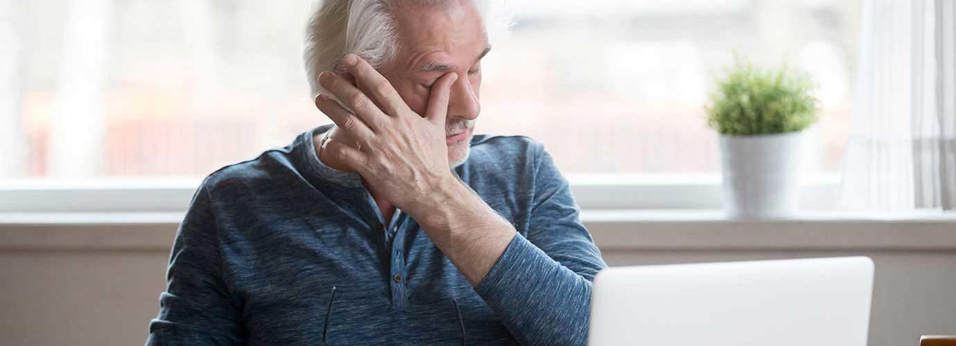 Oudere man zit achter een laptop zijn oog te krabben