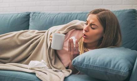 Vrouw ligt op de bank te hoesten terwijl ze kopje thee en een tissue vasthoudt