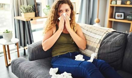 Vrouw met verkoudheids- of hooikoortssymptomen snuit haar neus