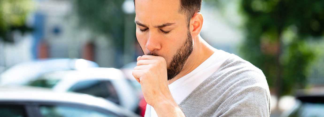 Man hoest buiten omringd door auto's